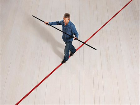 Man balancing on thin red line with pole Stock Photo - Premium Royalty-Free, Code: 649-03446882