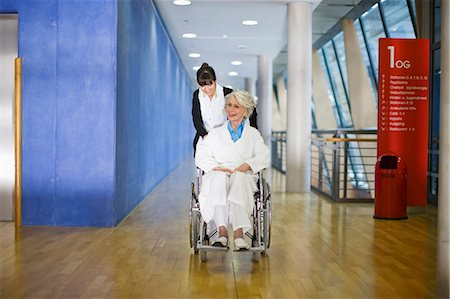 patient walking hospital halls - Old woman in a wheel chair and nurse Stock Photo - Premium Royalty-Free, Code: 649-03447150
