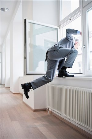 Businessman jumping out of window Stock Photo - Premium Royalty-Free, Code: 649-03447493