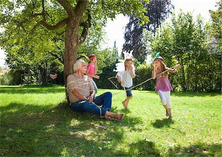 Grandchildren tie grandfather to tree Stock Photo - Premium Royalty-Free, Code: 649-03448397