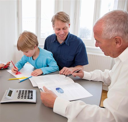 Advisor discussing papers with a father Stock Photo - Premium Royalty-Free, Code: 649-03465856