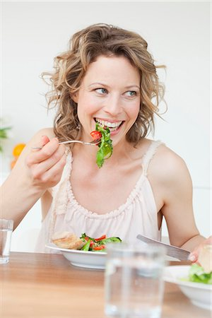 Woman eating mixed salad on table Stock Photo - Premium Royalty-Free, Code: 649-03487027