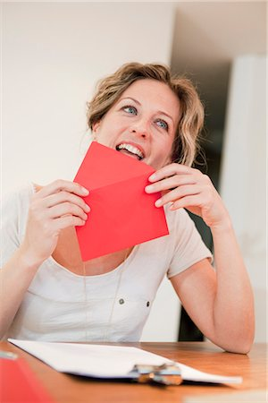 stamped - Woman licking on red envelope Stock Photo - Premium Royalty-Free, Code: 649-03487036