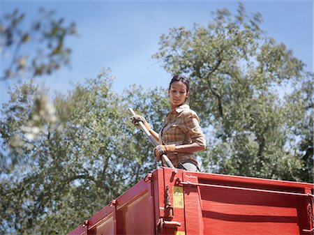 farmhand (female) - Woman in trailer with fork Stock Photo - Premium Royalty-Free, Code: 649-03487516