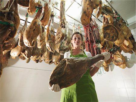 Woman holding a ham leg Stock Photo - Premium Royalty-Free, Code: 649-03487575