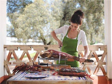 Woman slicing ham Stock Photo - Premium Royalty-Free, Code: 649-03487580
