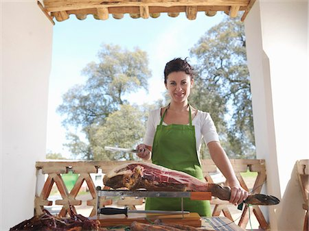Woman holding knife and ham leg Stock Photo - Premium Royalty-Free, Code: 649-03487582