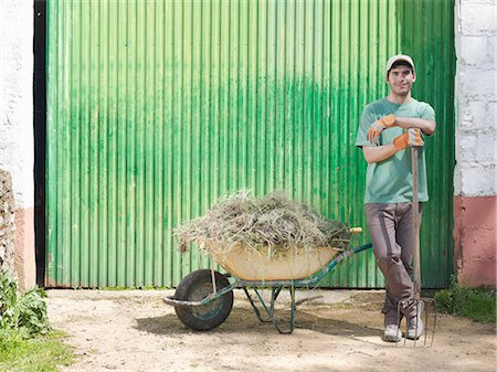 Man with wheelbarrow full of hay Stock Photo - Premium Royalty-Free, Code: 649-03487606