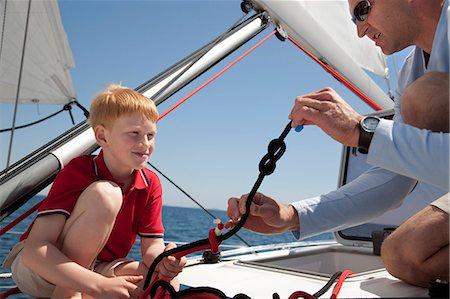 Man teaching boy knot on yacht Stock Photo - Premium Royalty-Free, Code: 649-03510980
