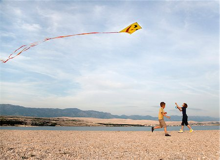 Children flying kite at beach Stock Photo - Premium Royalty-Free, Code: 649-03511053