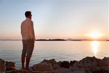 Man watching sun set at rocky beach Stock Photo - Premium Royalty-Free, Code: 649-03511118