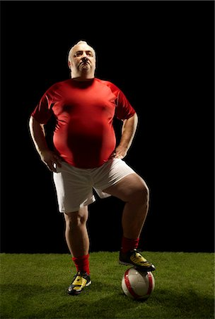fat man balls - Large sportsman with foot on football Stock Photo - Premium Royalty-Free, Code: 649-03511266
