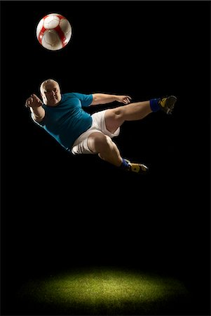 fat man balls - Large man doing flying volley Stock Photo - Premium Royalty-Free, Code: 649-03511275