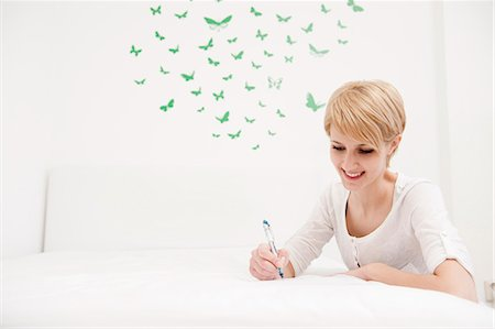 Young woman writing,sketching on bed Stock Photo - Premium Royalty-Free, Code: 649-03566140
