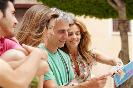 Two couples looking at postcard Stock Photo - Premium Royalty-Free, Code: 649-03566363