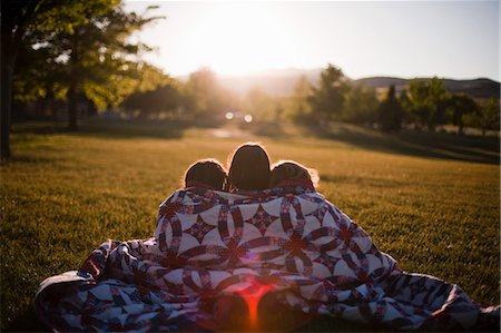 3 girls wrapped in blanket at sunset Stock Photo - Premium Royalty-Free, Code: 649-03566644