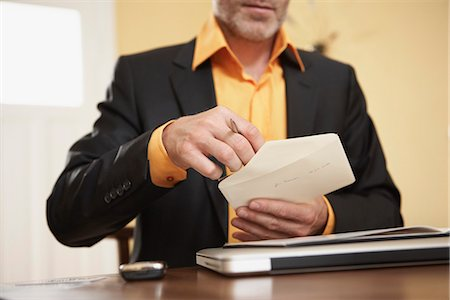 Man opening letter Stock Photo - Premium Royalty-Free, Code: 649-03606188