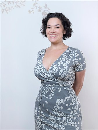 Curvy Woman standing up and smiling. Stock Photo - Premium Royalty-Free, Code: 649-03666807