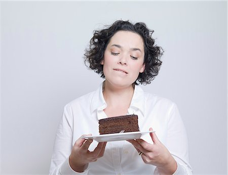woman looking at plate of cake Stock Photo - Premium Royalty-Free, Code: 649-03666825