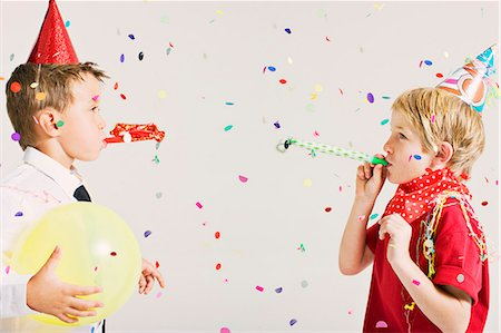 party boys blowing party blowers Stock Photo - Premium Royalty-Free, Code: 649-03667238
