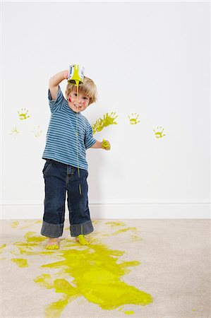 Toddler boy pouring paint onto carpet Stock Photo - Premium Royalty-Free, Code: 649-03667435