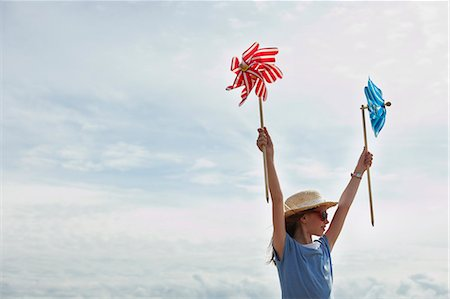 Girl holding windmills up in the sky Stock Photo - Premium Royalty-Free, Code: 649-03768908