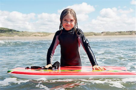 Young girl in the sea with surf board Stock Photo - Premium Royalty-Free, Code: 649-03768914