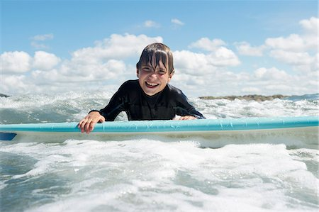 Young boy on surf board in the sea Stock Photo - Premium Royalty-Free, Code: 649-03768917