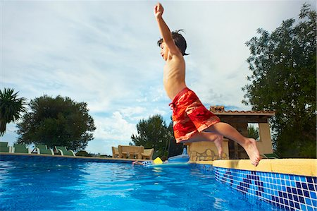 Young boy jumping into swimming pool Stock Photo - Premium Royalty-Free, Code: 649-03769630