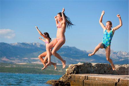 Girls jumping into water Stock Photo - Premium Royalty-Free, Code: 649-03769749