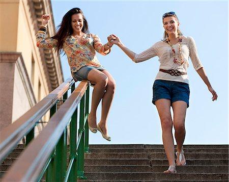 Young women sliding down railing Stock Photo - Premium Royalty-Free, Code: 649-03769776