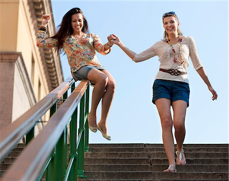 Young women sliding down railing Stock Photo - Premium Royalty-Free, Code: 649-03769776