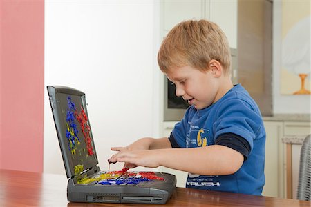 finger painting - Boy playing with paint on laptop Stock Photo - Premium Royalty-Free, Code: 649-03774402