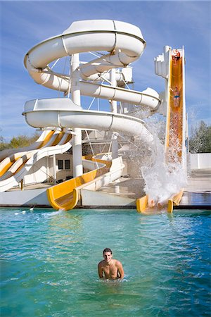 Man smiles in water at giant water slide Stock Photo - Premium Royalty-Free, Code: 649-03774837