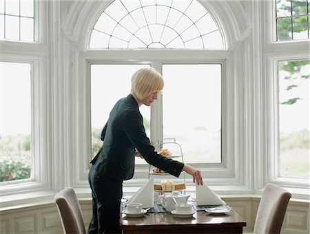Woman setting up table Stock Photo - Premium Royalty-Free, Code: 649-03775176