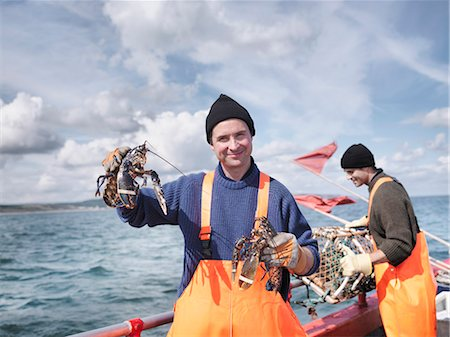 Fishermen on boat holding lobsters Stock Photo - Premium Royalty-Free, Code: 649-03770298