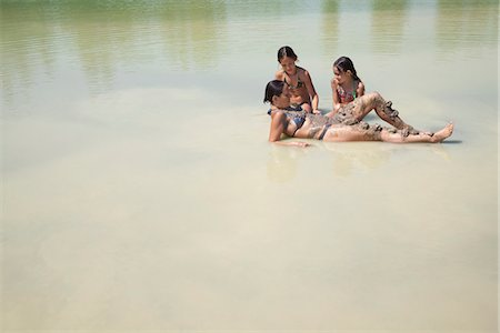 Mother and daughters play in a lake Stock Photo - Premium Royalty-Free, Code: 649-03771192
