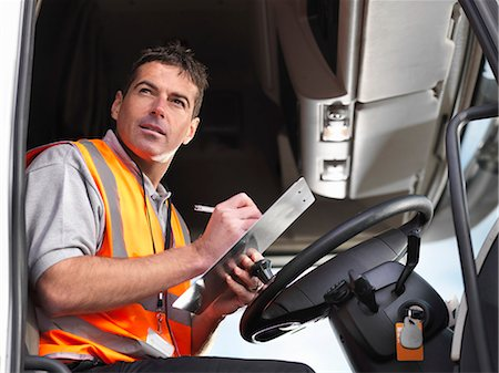 side view tractor trailer truck - Truck driver makes notes in truck cab Stock Photo - Premium Royalty-Free, Code: 649-03773427