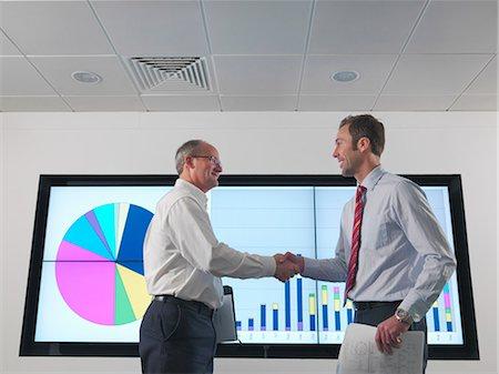 Businessmen shake hands with screen Stock Photo - Premium Royalty-Free, Code: 649-03773546