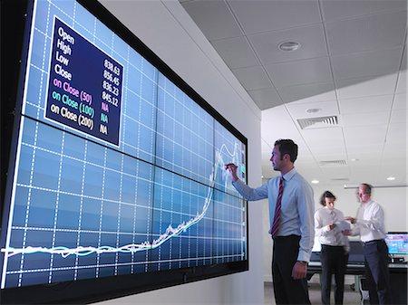 Businessman using graphs on screen Stock Photo - Premium Royalty-Free, Code: 649-03773551