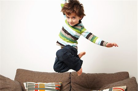 Young boy jumping on sofa Stock Photo - Premium Royalty-Free, Code: 649-03796075