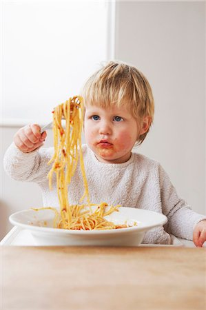 Messy baby boy eating spaghetti Stock Photo - Premium Royalty-Free, Code: 649-03796938