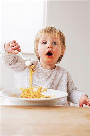 2 year old boy eating spaghetti Stock Photo - Premium Royalty-Free, Code: 649-03796939