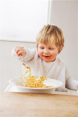 Happy baby boy eating spaghetti Stock Photo - Premium Royalty-Free, Code: 649-03796940