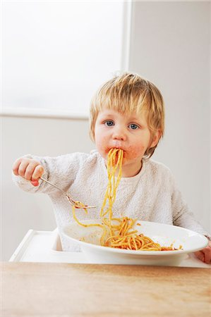 Messy baby boy eating spaghetti Stock Photo - Premium Royalty-Free, Code: 649-03796941