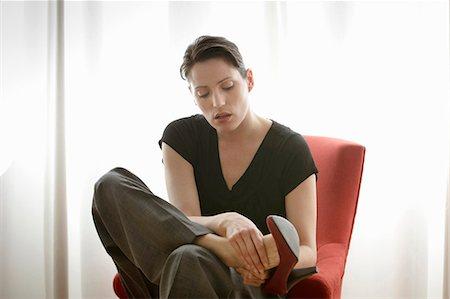 foot massage - woman rubbing her feet Stock Photo - Premium Royalty-Free, Code: 649-03796990