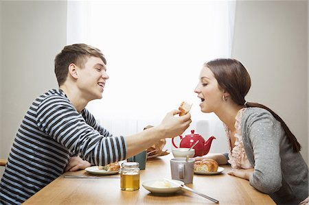 Man feeds girlfriend croissant at table Stock Photo - Premium Royalty-Free, Code: 649-03817181