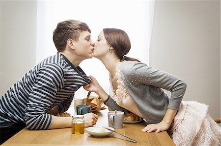 Woman kissing boyfriend over table Stock Photo - Premium Royalty-Free, Code: 649-03817182