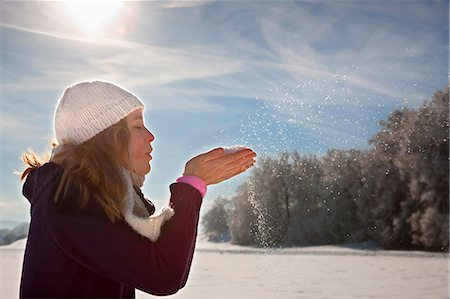 Woman blowing snow from hands Stock Photo - Premium Royalty-Free, Code: 649-03817453