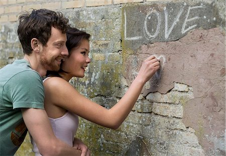 Girlfriend writing LOVE on a wall Stock Photo - Premium Royalty-Free, Code: 649-03817549